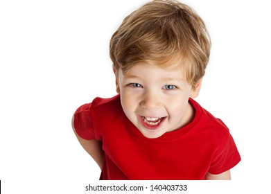 Cute boy looking up, smiling and laughing, wearing a red T-Shirt in a studio on a white background.
