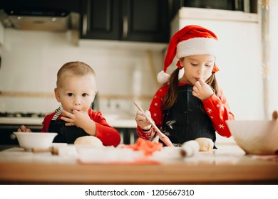 Cute boy and lovely girl in Christmas hat standing near kitchen table and sucking fingers while preparing delicious pastry for holiday