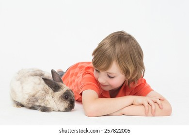 Cute boy lying down while looking at bunny on white background