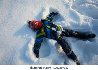 cute boy is making snow angel, top view