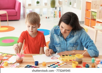 Cute boy with mother painting at table in room