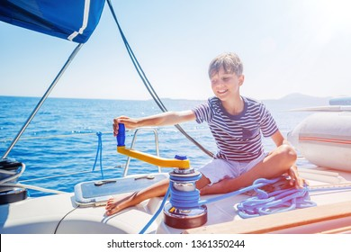 Cute boy on board of sailing yacht on summer cruise. Travel adventure, yachting with child on family vacation. Kid clothing in sailor style, nautical fashion. Focus on the Sailboat winch