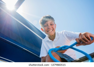 Cute boy on board of sailing yacht on summer cruise. Travel adventure, yachting with child on family vacation. Kid clothing in sailor style, nautical fashion.