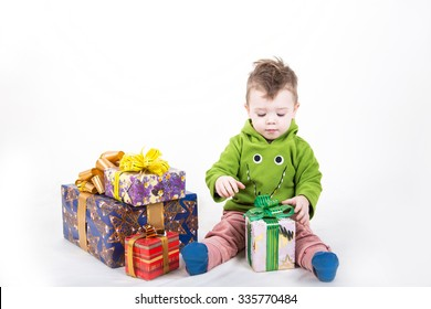 cute boy opens the box with gifts. Handsome happy kid sitting with padarkami on a white background