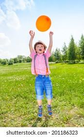 Cute boy with orange balloon in green field