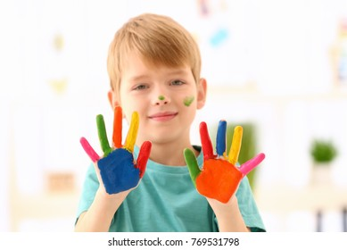 Cute boy with paint on hands against blurred background