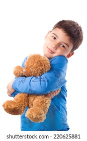 Cute boy in pajamas hugging a teddy bear