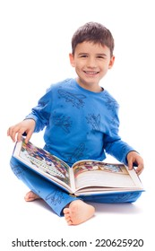 Cute boy in pajamas looking pictures in a book of fairy tales