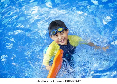 Cute boy playful on the pool and smiling at the camera