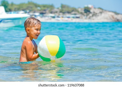 Cute boy playing with ball and swimming in the transparent sea