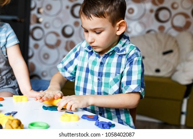 A cute boy playing with  color play dough and cutters. Having fun with colorful modeling clay. Creative kids molding at home. Children play with plasticine or dough.