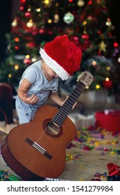 Cute boy is playing in front of a decorated Christmas tree with guitar