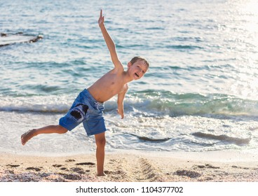 A cute boy playing on the beach at warm sunny summer day. Holidays fun summer vacation concept