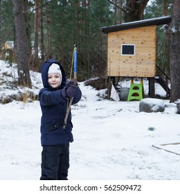 Cute boy playing outside with hand made bow,winter time