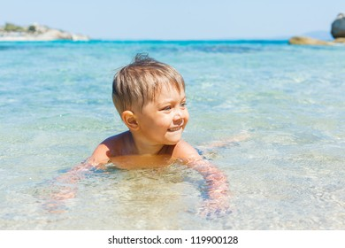 Cute boy playing and swimming in the transparent sea