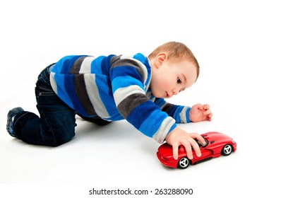 Cute boy playing with toy car