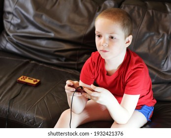 Cute boy playing video games at home, hobby