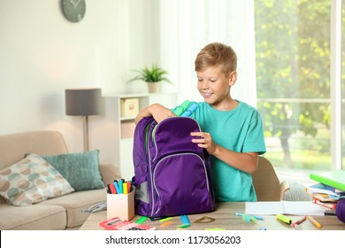 Cute boy putting school stationery into backpack at table indoors