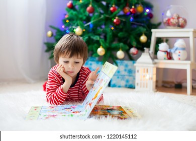 Cute boy, reading a book in front of Christmas tree at home