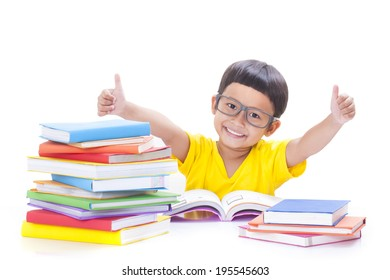 Cute boy is reading a book and showing thumb up sign.