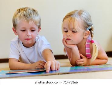cute boy reads to adorable little blonde girl in school