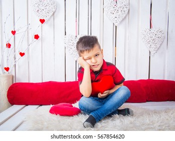 Cute boy in red and black striped T-shirt and jeans on a light background with hearts
