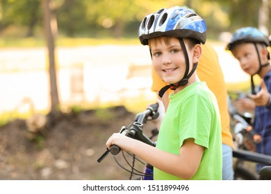 Cute boy riding bicycle outdoors