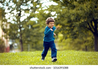 Cute boy running across grass und smiling.