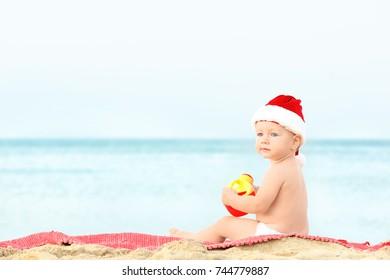 Cute boy in Santa hat on beach
