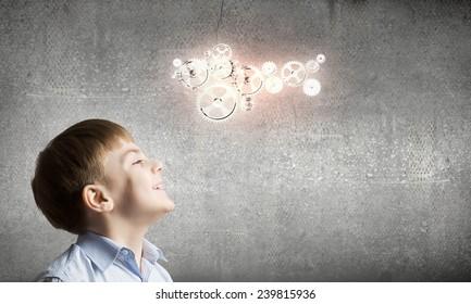Cute boy of school age looking up at gears mechanism