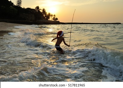 Cute boy in shorts and a Santas cap standing knee-deep in the sea and throws the bait, waiting for the catch. Against the background of the sun goes down, wonderful golden sheen on the sea surface