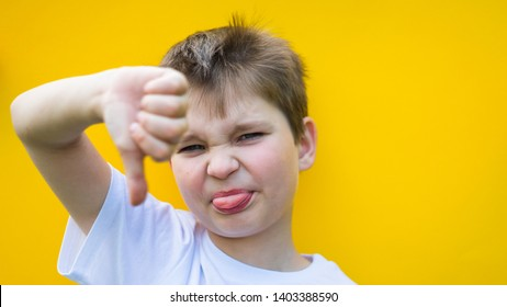 cute boy showing blurred thumb down. focus on face. child showing his tongue. childhood, expressions and school concept