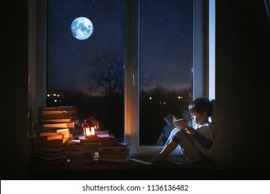 A cute boy sits on the windowsill at night. The child reads books under the moonlight. The window shows the moon and stars.