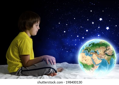 Cute boy sitting in bed holding Earth planet. Elements of this image are furnished by NASA