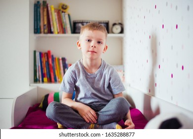 cute boy sitting on the bed at home, look at camera