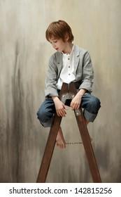 Cute boy sitting on ladder