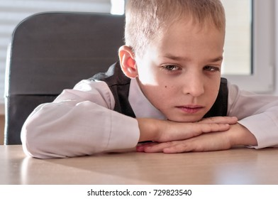 Cute boy sitting at a table. He put his head on the folded hands lying on the table. Close-up portrait of a pensive schoolboy in a business suit.