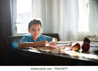 Cute boy sitting at a table at home and does homework. A child draws and writes. He draws a beautiful card for mother. Healthy eating for children.