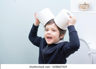 Cute boy sitting in the toilet playing with toilet paper,kid boy sitting in the restroom and putting  toilet roll on his head, Child holding two white tissue, Children health care concept