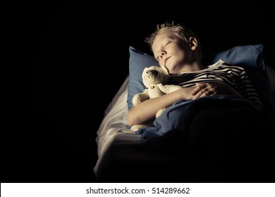 Cute boy sleeping in bed with plush toy bear in room with dark area for copy space