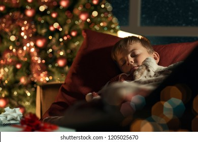 Cute boy sleeping in the living room next to the Christmas tree and waiting for Santa on Christmas Eve