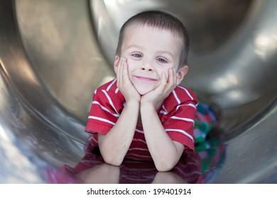 Cute boy, sliding down the slide, smiling