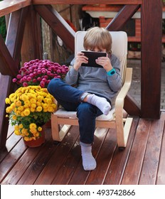 Cute boy with smart watch sitting on terrace and reading electronic book