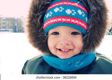 Cute  boy is smiling outdoor snow winter. Christmas time