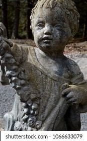 A cute boy stone statue graces the garden.