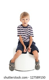 Cute boy in a striped T-shirt and blue shorts sitting on a white chair and holding an invisible joystick. Studio shot, isolated on white background.