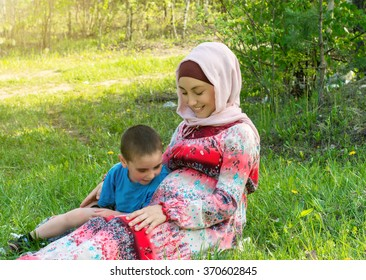 Cute boy stroking mum's pregnant belly at the park