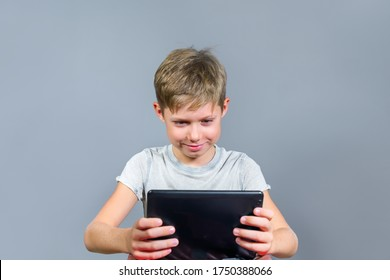 Cute boy is studing online through tablet at home. Remotely study. Distance education. Back to school. Stay at home. Quarantine. Unschooling