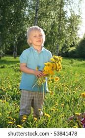 Cute boy with sunflowers in field