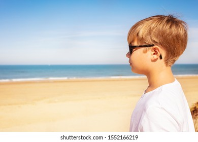 Cute boy in sunglasses on beach side portrait